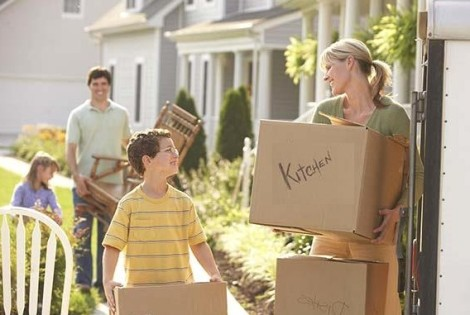 Family putting moving boxes into truck